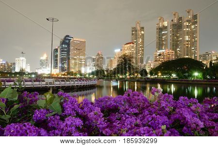 Cityscape view of modern buildings at Benjakitti garden at twilight time where have the light of the lamps shining on the pool and buildings. Bangkok Thailand.