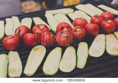 Vegetable vegan barbecue roasted on metal grill grate. Diet bbq. Zucchini and tomatoes closeup at picnic outdoors