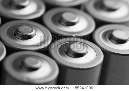 low angle black and white close up of electric batteries and accumulators AAA AA with selective focus on top