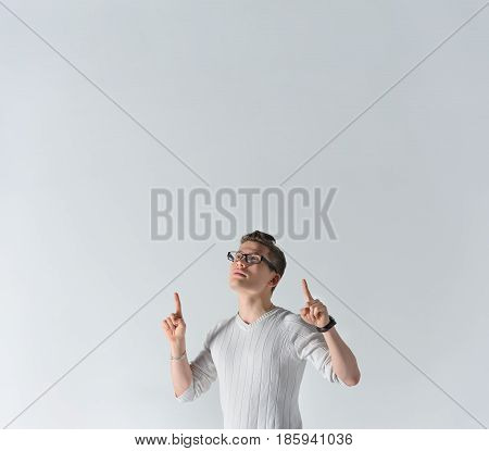 Handsome young caucasian man pointing up with index fingers upwards, looking up, standing against gray background in studio. Positive thinking. Emotions, facial expression symbols, sign, body language