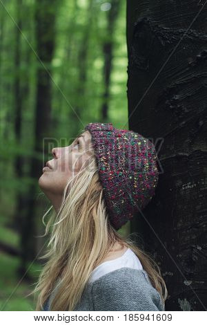 vertical side view portrait of Caucasian young woman with long blonde hair and colorful wool hat leaning against a tree in a green forest and looking up