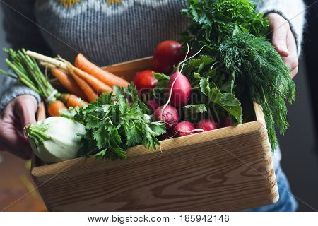 closeup of young Caucasian woman with grey woven sweater holding a large wooden crate full of raw freshly harvested vegetables
