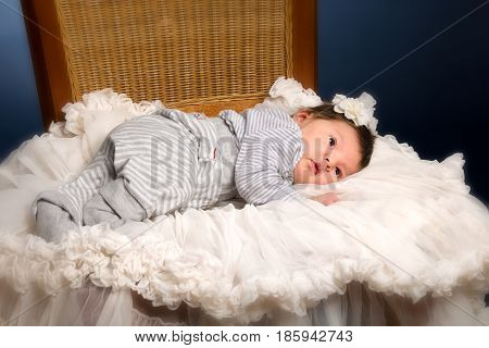Newborn baby girl with white blanket posed and sleeping on a wooden chair