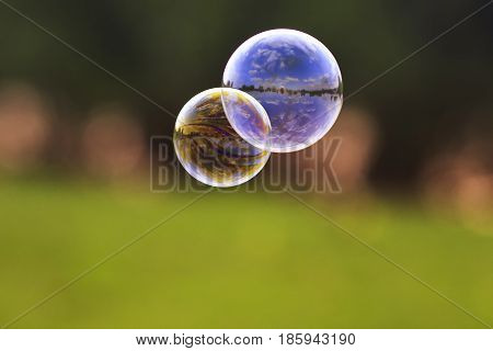 two bright bubble with shiny reflections on the background of green meadows