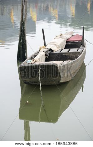 A wooden boat on calm water within the Huangpu Ancient Port scenic area in the city of Guangzhou China in Guangdong province on an overcast day.
