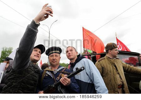 Orel Russia - May 9 2017: Victory Day selebration. Young men making selfie with mariner with red flags background