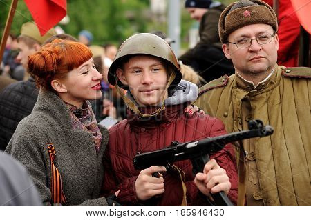 Orel Russia - May 9 2017: Victory Day selebration. Red haired girl and young man in Soviet war helmet with rifle taking photo