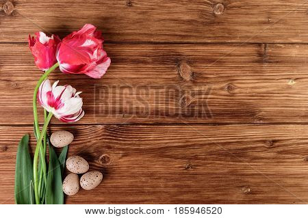 Tulips flowers and eggs decoration over wooden background. Top view text space