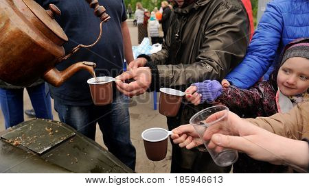 Orel Russia - May 9 2017: Victory Day selebration. People reaching for tea from old copper kettle closeup
