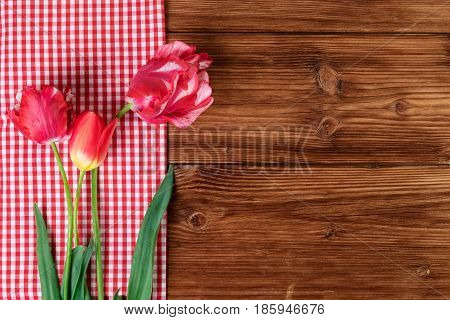 Tulips with red checkered tablecloth on country wooden background. Top view text space