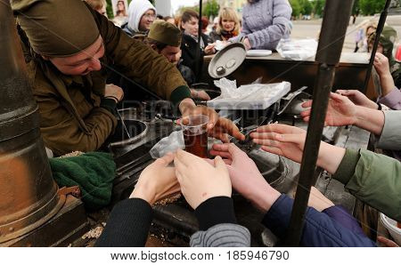 Orel Russia - May 9 2017: Victory Day selebration. People reaching for glass of tea from Soviet field kitchen closeup