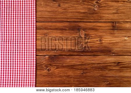 Red checkered tablecloth on old wooden background. Top view text space