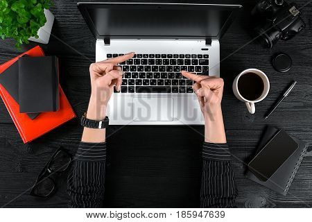 Woman working at the office table. Top view of human hands, laptop keyboard, a cup of coffee, smartphone, notebook and a flower on a wooden table background. Woman shows indecent gestures with her hands