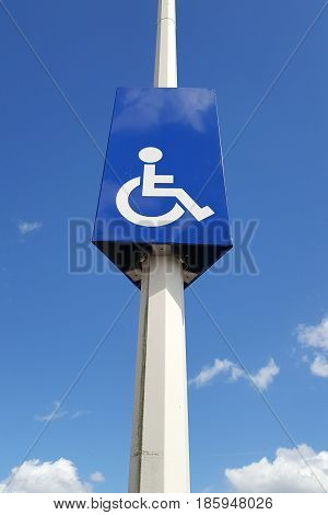Mast With A Road Sign With A Parking Space Reserved For The Disabled