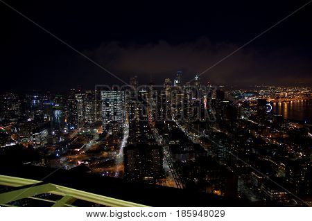 SEATTLE, WASHINGTON, USA - JAN 23rd, 2017: skyline of downtown Seattle, view from the top of the Space Needle during a cloudy night, city lights.