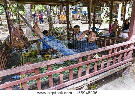 Phnom Kulen, Cambodia - January 3, 2017: Cambodian guys resting under a gazebo in Phnom kulen national park. Phnom Kulen is a national park in Siem Reap Province, famous for some waterfalls