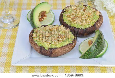 Healthy avocado stuffed portobello mushrooms with chopped walnuts. Top macro view.