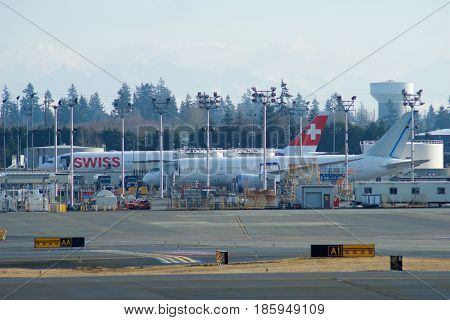 EVERETT, WASHINGTON, USA - JAN 26th, 2017: Boeing production site, the huge factory at Snohomish County Airport or Paine Field, a brand new SWISS B777 and a B787 Dreamliner in the background.
