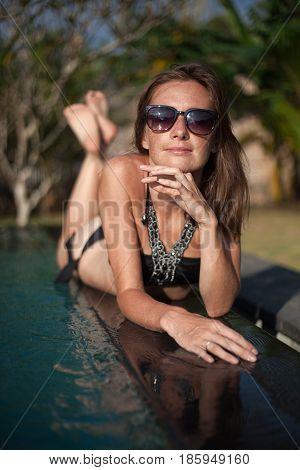 Vertical portrait of beautiful girl in black bikini and sunglasses lying on the pool edge