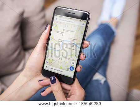 UZHGOROD, UKRAINE - MAY 11, 2017: New black iPhone 7 Plus, with Google Maps in the hands of the woman sitting on the couch, on May 11, 2017 in Uzhgorod, Ukraine.