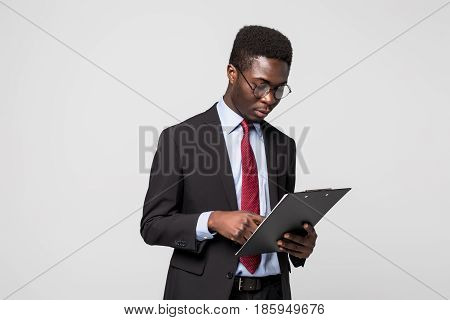African American Businessman Writing On A Clipboard On Grey