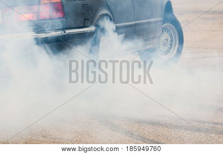 Car from side with detail on spinning wheel smoking and doing burnouts tire