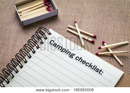 Camping checklist concept on notebook with match box and wooden matches