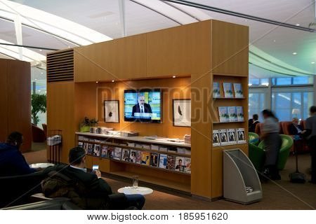 TORONTO, CANADA - JAN 28th, 2017: Air Canada Maple Leaf Lounge at YYZ airport International, seating area with colored leather chairs and newspapers and a TV, airport interior for frequent flyer