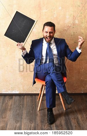 blackboard in hands of angry shouting teacher man or businessman in suit empty chalkboard for copy space