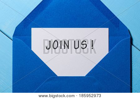The words JOIN US written in vintage blue envelope.