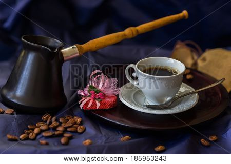Cup of fresh hot coffee, turk, coffee beans, chocolate candy in the shape of a heart. Low key image. Concept of valentines, good mood and other greeting cards.