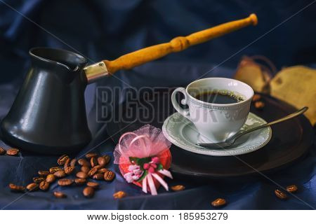 Cup of fresh hot coffee, turk, coffee beans, chocolate candy in the shape of a heart. Low key image. Selective focus. Concept of valentines and other greeting cards.