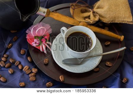 Cup of fresh hot coffee, offee beans, turk, chocolate candy in the shape of a heart on dark wooden background. Low key image in vintage style. Concept of valentines and other greeting cards