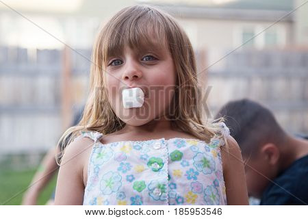 Young 5 year old girl eating marshmallow during hot spring evening.