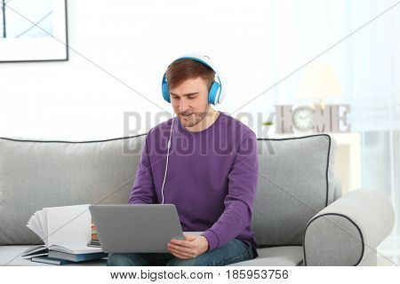 Concept of audiobook. Handsome young man with headphones and laptop sitting on sofa at home