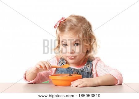 Cute little girl eating yogurt with cornflakes on white background
