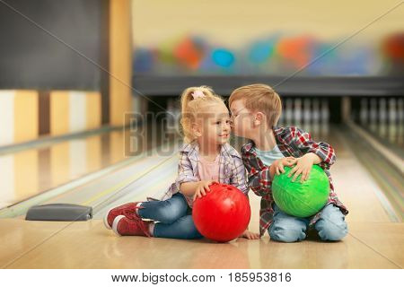 Cute little children with balls sitting on floor in bowling club