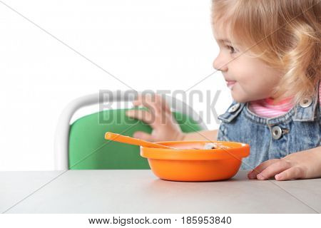 Cute little girl with yogurt and cornflakes on white background