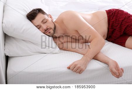 Man sleeping on two pillows at home. Incorrect sleep posture concept