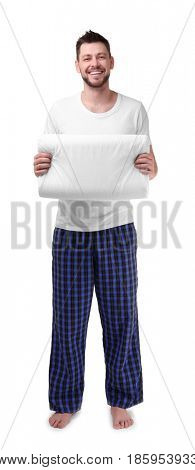 Young happy man in pajamas holding orthopedic pillow on white background