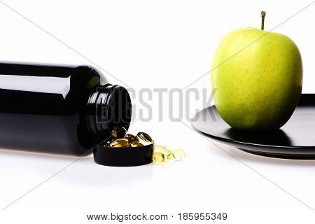 Green Apple Fruit And Fish Oil In Black Plastic Bottle