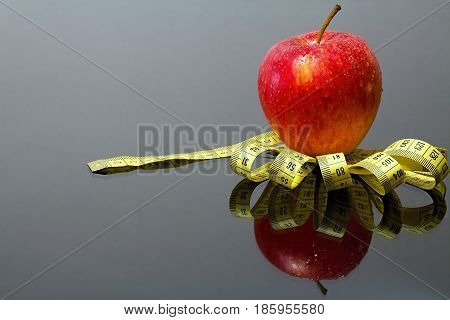 Fresh red apple with drops of water on a measuring tape with mirror reflection. Red apple measuring tape and mirror.