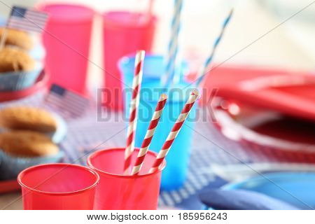 Colorful plastic cups with straws on table