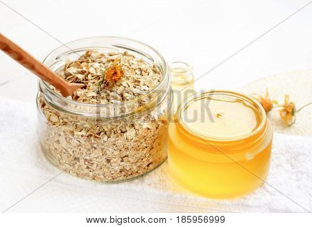 Home spa skincare ingredients. Glass jars of oatmeal flaks and yellow honey, white bathroom towel.