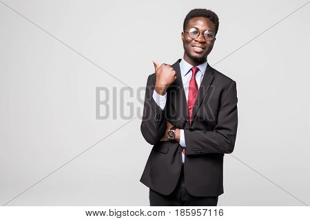 Handsome Young African Man In Formalwear Pointing Away And Smiling While Standing Against Grey Backg