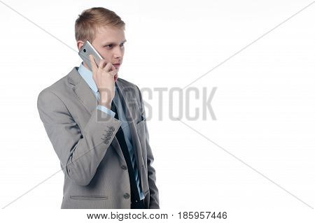 a young guy talking on the phone. in a business suit on a white background.