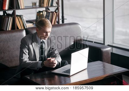 young businesswoman working at a laptop sitting at the table. looks at the notebook and folded his hands on the table.