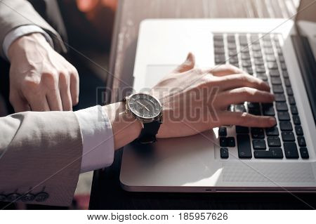 businessman typing on laptop. working at the laptop. in the hands of expensive watches out the window the sun is shining.