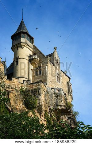 Swallows flying around spooky medieval Chateau de Montfort castle built upon the cliffs along Dordogne river in Vitrac Perigord province in France.
