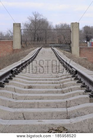 Railroad tracks leading to a metal gate in the city of Zhaodong China in Heilongjiang Province on an overcast day.